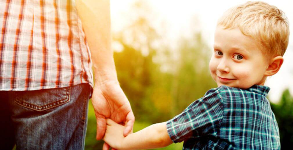 Photo of a young boy looking over his shoulder while holding hands with an adult