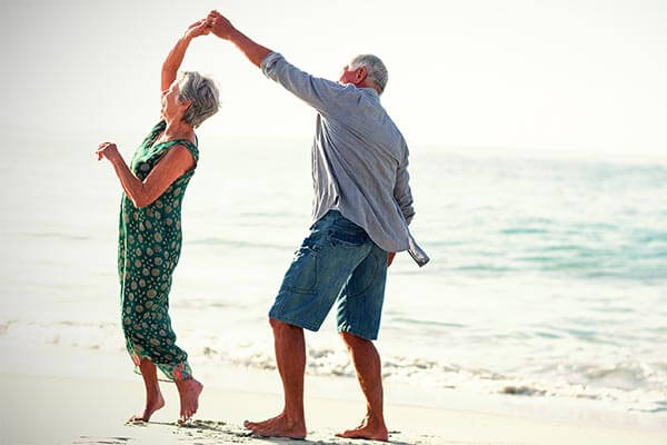 Retired couple dancing on the beach